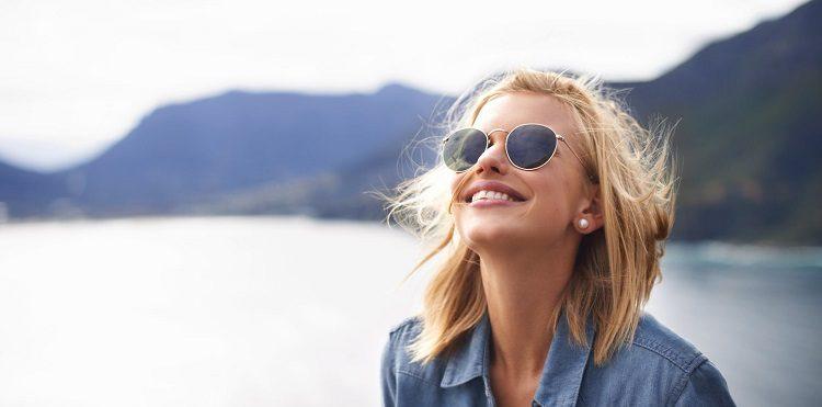 Kobieta w okularach uśmiechnięta.
